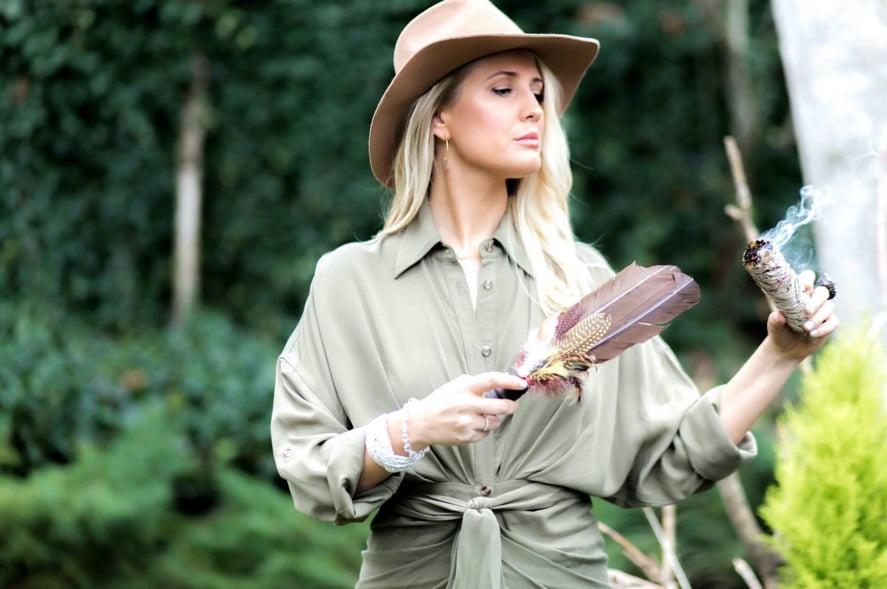 Casey Stevens holding feather burning sage